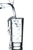 Rent vatten hällde från en tillbringare in i ett exponeringsglas Arkivbild