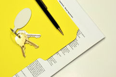 Rental agreement and apartment keys. Lease agreement document in a yellow folder with the apartment keys Stock Image