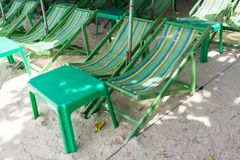 Rental beach canvas chairs and green table on natural white sand. With tree shadow Stock Images