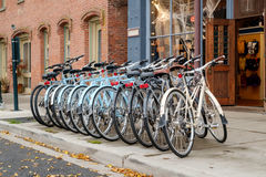 Rental bicycles. Port Townsend, WA, USA October 31, 2016: Row of rental bicycles lined up on sidewalk outside of cycle store Royalty Free Stock Images