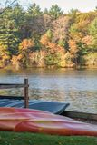 Rental canoes and kayaks along lakefront in autumn royalty free stock photography