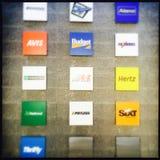 Rental car company logos. Collage of rental car company logos hanging on wall royalty free stock photo
