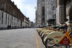 Rental citybikes branded EXPO Milano 2015 are parked at the station near Duomo of Milan. stock image