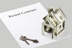 Rental contract is a blank on a gray background. And objects describing the sale or purchase of a home. Focus on 'Rental Contract Stock Photo