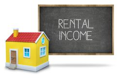 Rental income text on blackboard with 3d house Stock Image