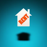 Rental property. An icon of a house hovers in the air, casting a shadow on blue background. The word `rent` is inscribed in the silhouette of the house Stock Image