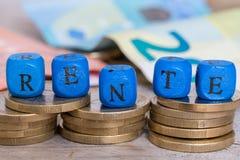 Rente em cubos alemães da letra da pensão no conceito das moedas imagem de stock