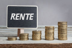 Rente pensions in German language with money stacks. Rente pensions in German language, white chalk type on black board, Euro money coin stacks of growth on wood Stock Images