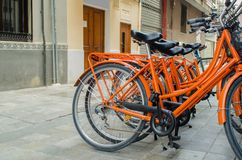 Renting orange bike on the street in Valencia stock photography