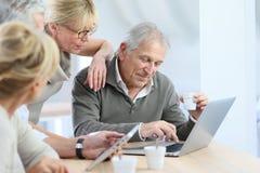 Rentner zu Hause mit Laptop und Tablette Stockfotografie