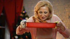 Rentnerdame, die gebratenes Huhn, Weihnachtslichter funkeln auf Hintergrund riecht stock video