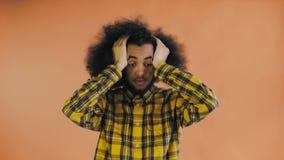 Renversement afro-américain triste de sentiment d'homme sur le fond orange regardant la caméra Concept des ?motions banque de vidéos