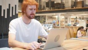 Renversement d'homme de barbe par la perte de travail se reposant dans l'ordinateur portable image stock