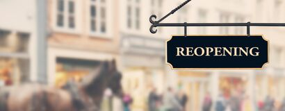 Free Reopening Economy Concept. Sign With Word Reopening Hanging Against Open Shop Windows Background. Restarting Business Royalty Free Stock Photography - 183294027