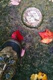 Repère d'USGS et botte de randonneurs avec des feuilles d'automne images libres de droits