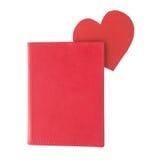 Repère de papier rouge de coeur à l'intérieur d'un livre rouge d'isolement sur le blanc Images libres de droits