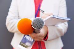 Repórter fêmea na conferência de imprensa, escrevendo as notas, guardando microfones fotografia de stock