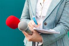 Repórter fêmea que toma notas na conferência de imprensa journalism foto de stock