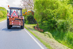 REPÚBLICA CHECA, DOBRANY, EL 26 DE MAYO DE 2016: Hierba de siega de la máquina del tractor a lo largo del camino foto de archivo libre de regalías