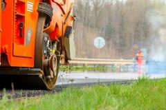 REPÚBLICA CHECA, PLZEN, O 7 DE MAIO DE 2016: Asfalte a máquina e o rolo de espalhamento da vibração em trabalhos de estrada do pa Foto de Stock