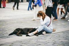 República Checa, Praga, el 25 de julio de 2017: Un pintor hermoso de la mujer joven se sienta en el piso en el medio del cuadrado foto de archivo libre de regalías
