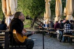 República Checa Praga 11 04 2014: música del juego del músico de la calle cerca del río en un restaurante para las huéspedes imagen de archivo libre de regalías