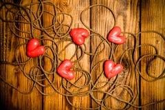 Rep och röda hjärtor på den gamla träbrända tabellen eller brädet för baksida royaltyfria bilder