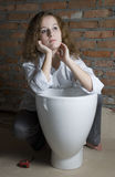 Repair. A young girl sits near a toilet opposite a brick wall Royalty Free Stock Images