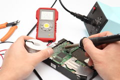Repair. Men's hands with soldering iron and hard disk royalty free stock image