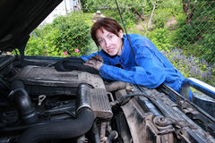 Repair. The young beautiful girl who has soiled the person and hands in lubricating oil, repairs the car royalty free stock images