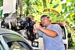Repair of the accepted engine of the car by one man - mechanic. Repair accepted engine car one man mechanic royalty free stock photos