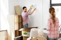 Happy couple moving to new home and hanging photo stock photography