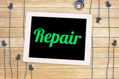 Repair against plug and tablet on wooden background Royalty Free Stock Photo