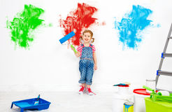 Repair in apartment. Happy child girl paints wall. Repair in the apartment. Happy child girl paints the wall with blue paint Royalty Free Stock Image