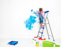 Repair in apartment. Happy child girl paints wall. Repair in the apartment. Happy child girl paints the wall with blue paint Royalty Free Stock Images