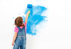 Repair in apartment. Happy child girl paints wall. Repair in the apartment. Happy child girl paints the wall with blue paint Stock Photography