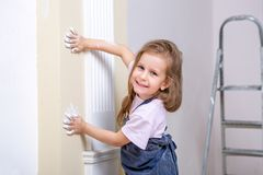 Repair in the apartment. Happy family mother and daughter in aprons paint the wall with white paint. The girl leaves traces of han royalty free stock image