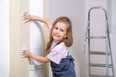 Repair in the apartment. Happy family mother and daughter in aprons paint the wall with white paint. The girl leaves traces of han royalty free stock photos