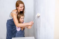 Repair in the apartment. Happy family mother and daughter in aprons paint the wall with white paint. Mother helps her daughter to stock photo