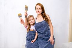 Repair in the apartment. Happy family mother and daughter in aprons prepared to paint the wall with white paint. Sit with tassels stock photos