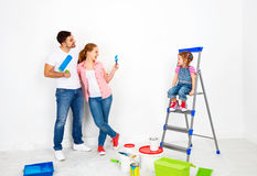 Repair in apartment. Happy family mother, father and child daughter paints wall . stock photos