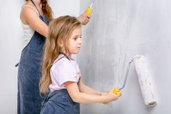 Repair in the apartment. Happy family mother and little daughter in blue aprons paints the wall with white paint. Daughter paints stock photos