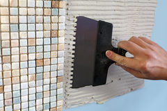 Repair in the apartment: installing the mosaic tile on the wall Stock Photos