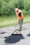 Repair of asphalt blade road. Unknown road worker level asphalt mixture for repair of asphalt covering country road Stock Photo
