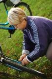 Repair a bike. Woman repairs a blue bike Royalty Free Stock Image