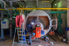 Repair of the boiler. Worker repairing the boiler with the aid of welding Stock Image
