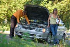Repair of the broken car. The guy repairs the car, the girl stands nearby Royalty Free Stock Images