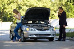 Repair of the broken car. The guy repairs the car, the girl stands nearby Stock Photography