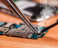 Repair a broken mobile phone closeup. On wooden background stock images