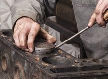 Repair car engine. Car mechanic repairing an internal combustion engine Royalty Free Stock Images